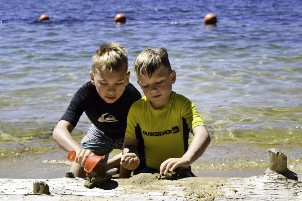 Kids playing on beach at Payette Lake, McCall, Idaho