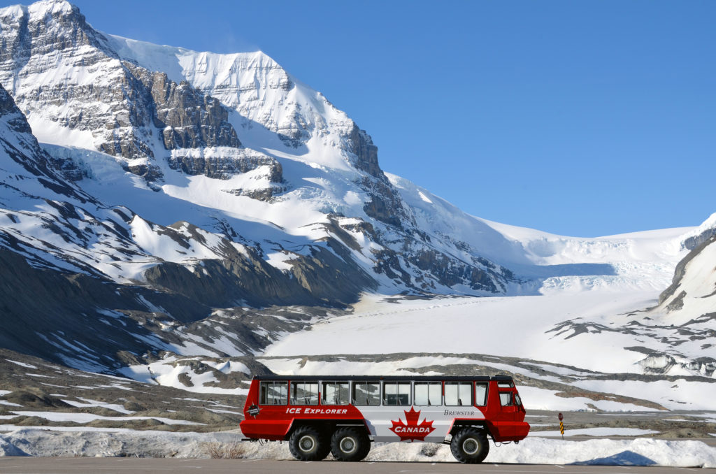 Parking snowcoach, used for tours in front of the Athabasca Glacier at the Columbia Icefield.