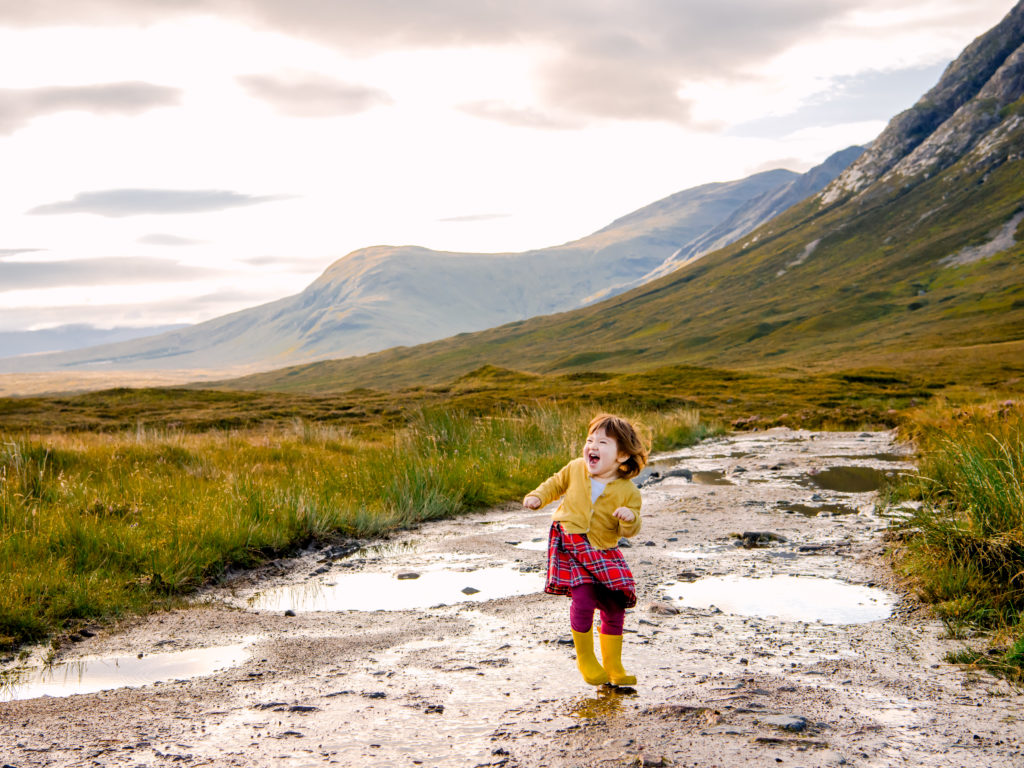 Child playing in puddles in Glencoe, Scotland