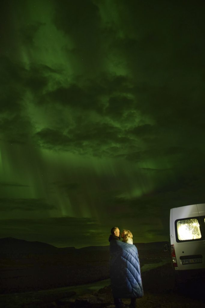 Couple cuddled up watching Northern Lights off side of road in North Iceland